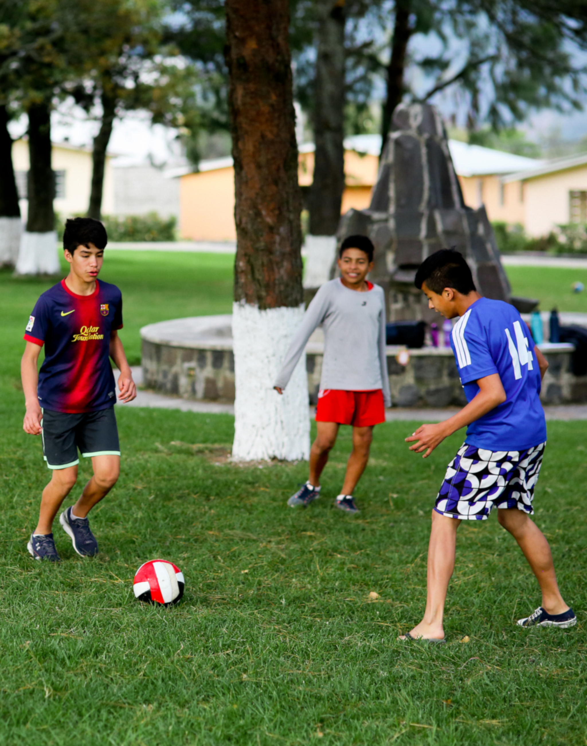3 boys playing soccer in the main field